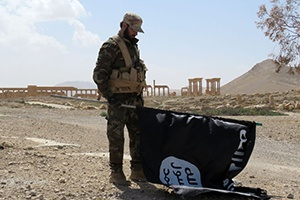 A member of the Syrian pro-government forces carries an Islamic State flag