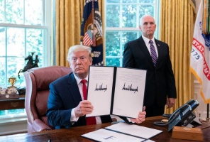 Trump displaying his signature on an executive order