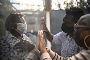 family with face masks touching hands through protective barrier